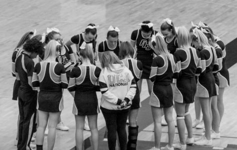 Head Coach Carrie Kihn huddles with her team. Kihn has been coaching cheer at Fairmont for 19 years.